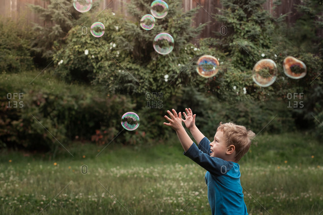 Little boy trying to catch bubbles