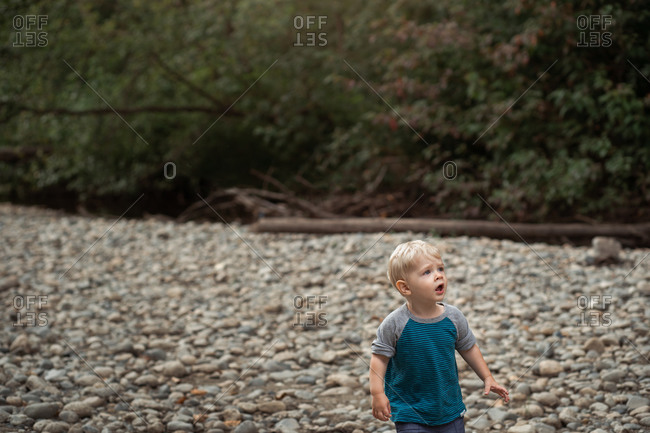 Toddler boy looks amazed as her ventures on a rocky riverbank