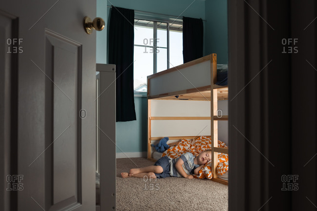Little boy fast asleep lying on the floor with his head on bed