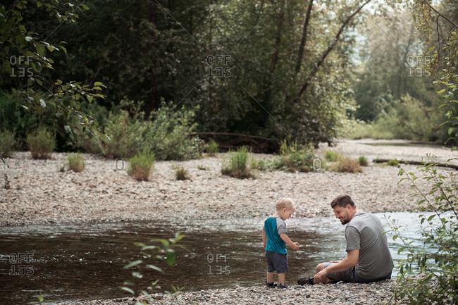 Father and son together on riverbank throwing stones into water