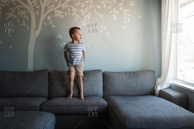 Little boy jumping on couch while looking out window