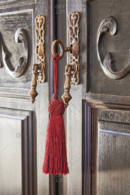 Close up of a tassel keychain hanging from old wooden door