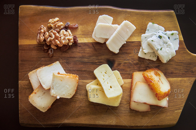 Cheese platter with different sorts of Portuguese cheese, walnuts and raisins