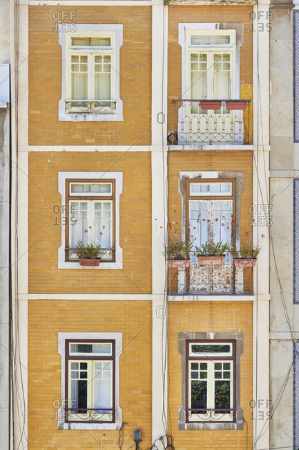 Facade of yellow brick buildings in downtown Lisbon