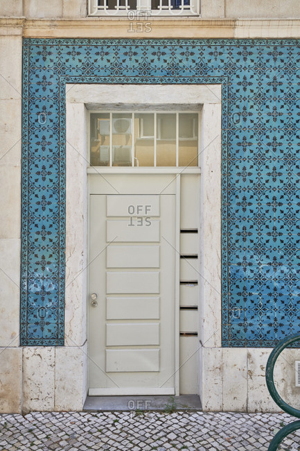 White door surrounded with decorative blue tile in the Principe Real neighborhood, Lisbon, Portugal