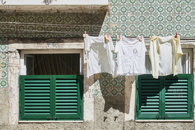 Laundry hanging outside window with green shutters on an old apartment building in Lisbon