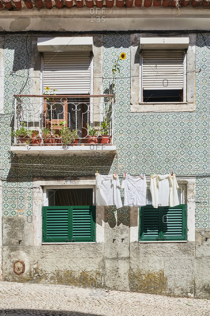 Laundry hanging from old apartment window in Lisbon