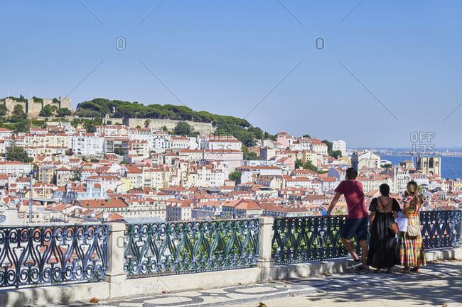 Tourists overlooking Lisbon and the Tagus river from Miradouro de Saeo Pedro de Alcantara, Portugal