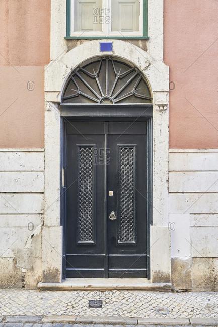 Black door on pink home in the Santa Catarina neighborhood, Lisbon, Portugal