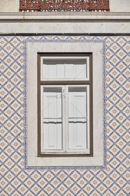 Home exterior with decorated tile around the window, Santos neighborhood, Lisbon, Portugal