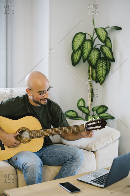 Smiling man learning to play guitar online at home