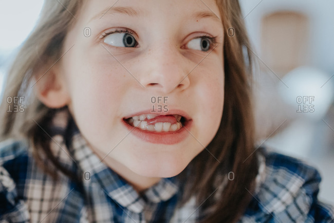 Young girl sticking her tongue through gap in her front teeth