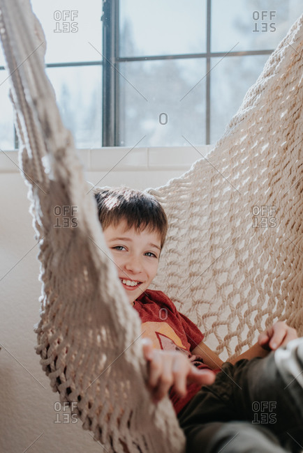 Boy smiling and sitting in a macrame chair
