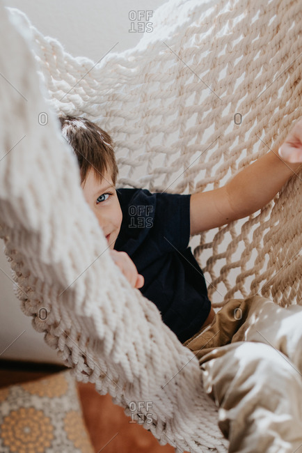 Young boy smiling and sitting in a macrame chair
