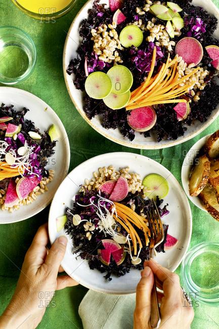 Person eating purple kale farro salad with Meyer lemon vinaigrette