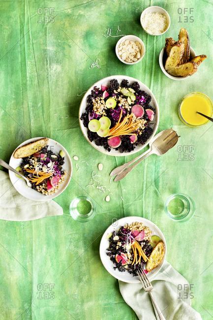 High angle view of purple kale farro salad with Meyer lemon vinaigrette on green background