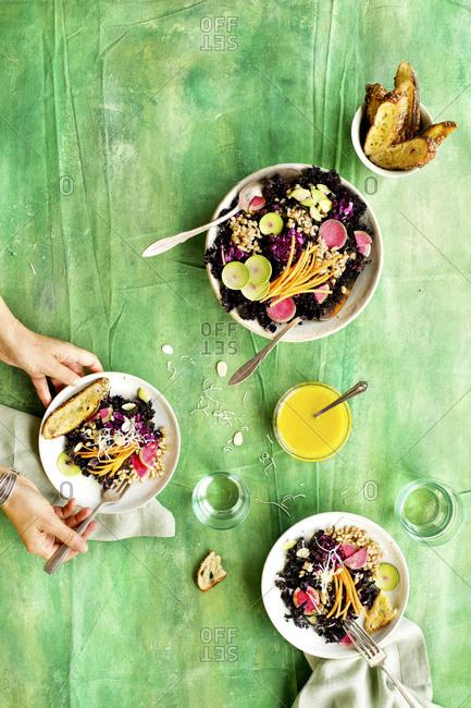High angle view of person eating purple kale farro salad with Meyer lemon vinaigrette