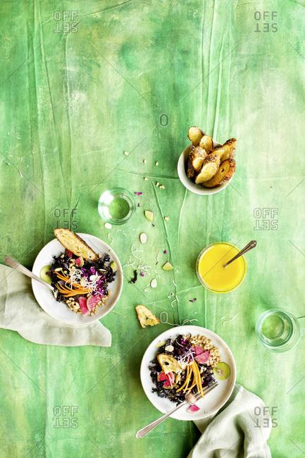 Overhead view of purple kale farro salad with Meyer lemon vinaigrette on green background