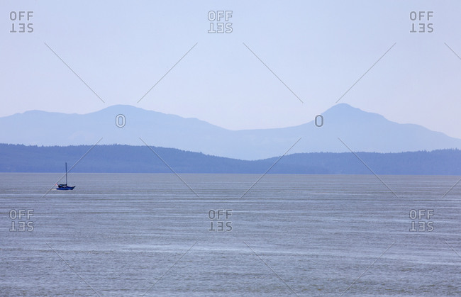 Sailboat on the Strait of Georgia with Vancouver Island hills in the background