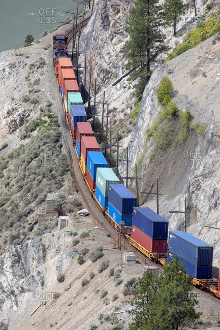 British Columbia, Canada - July 21, 2020: Bird's eye view of a train on the Canadian National Railway carrying containers at Fraser Canyon
