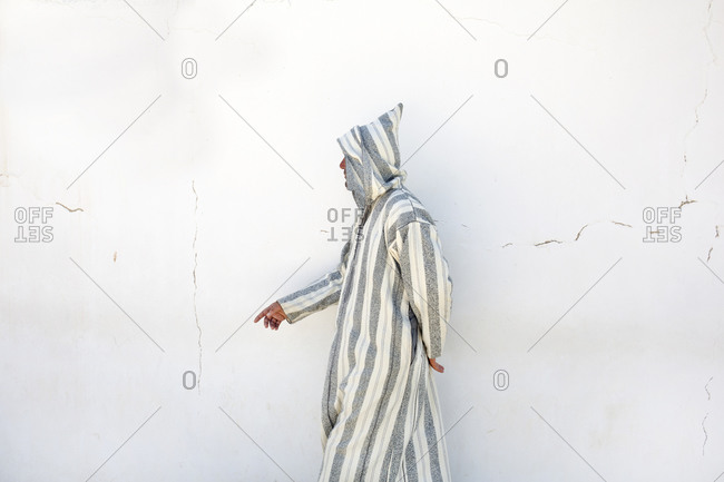 Marrakesh, Morocco - April 7, 2019: Man walking by white wall in market place