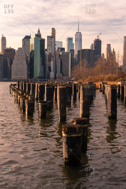 Modern high rise buildings of New York City seen from waterfront of Brooklyn Bridge Park at sunset time
