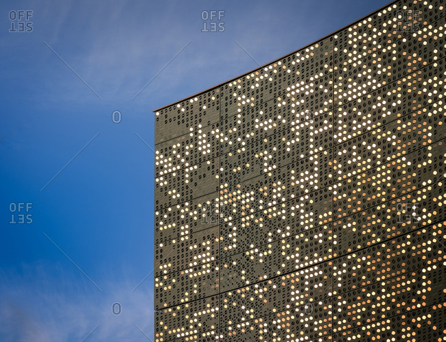 March 5, 2020: From below of contemporary high rise office building with illuminated windows against blue sky in New York City