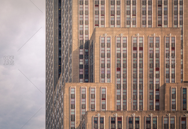March 5, 2020: Low angle of tall commercial concrete building with modern architecture against cloudy sky on street of New York City
