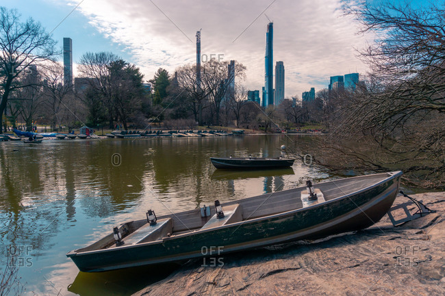 Old wooden boat moored on river shore with contemporary skyscrapers in background in spring day in New York City