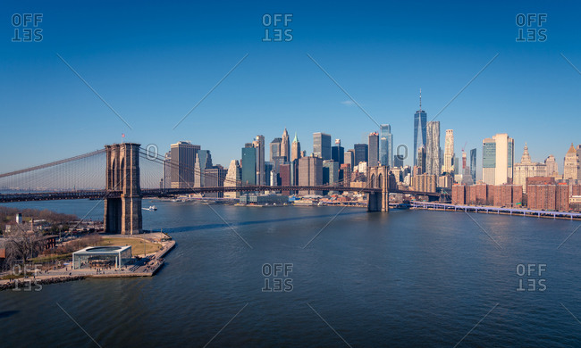 Amazing New York city skyline with famous Brooklyn bridge over river against cloudless blue sky in sunny day