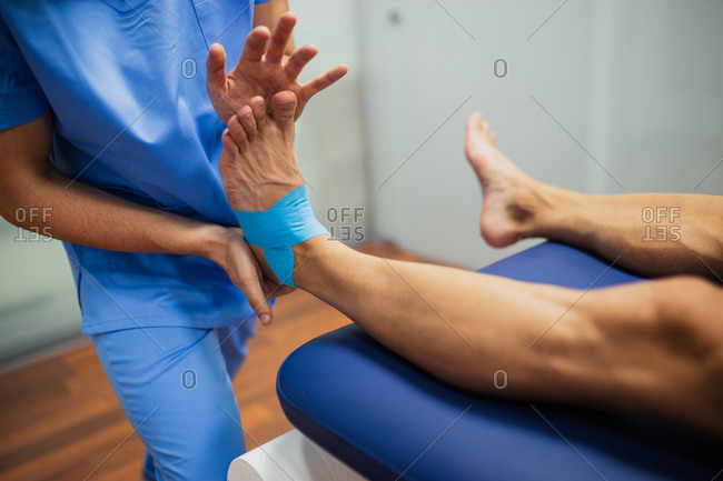 Top view of crop unrecognizable chiropractor in blue uniform attaching kinesio tape on foot of faceless man lying on examination couch in clinic