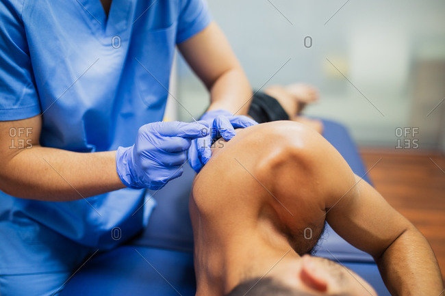 From above of crop faceless sports medicine doctor in sterile gloves inserting thin needle in the back of unrecognizable male patient in underwear lying on examination couch during acupuncture process
