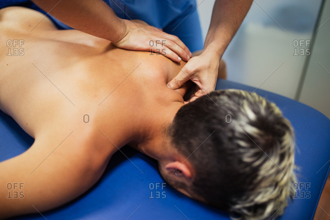 Osteopath in blue uniform examining back of unrecognizable slim male patient with dyed hair lying on examination table in clinic