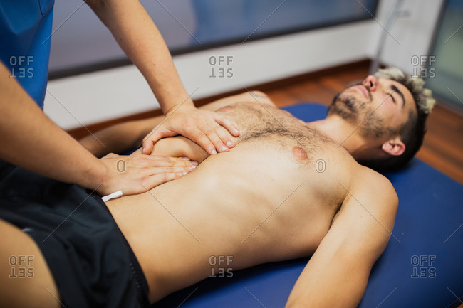 From above of crop anonymous osteopath checking up thorax of slim man in underwear lying on examination couch with closed eyes