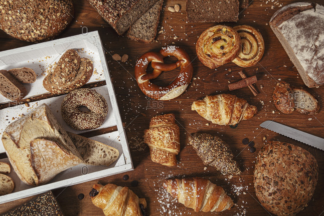 Top view of composed homemade buns and loaves with croissants and other bakery on wooden table