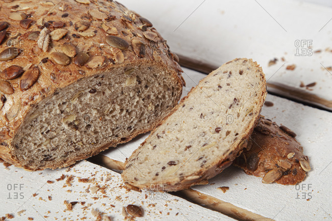 From above round rye bread loaf with few cut slices on wooden table with knife