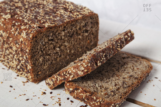 Closeup of homemade loaf of rye bread with sesame seeds cut in few slices