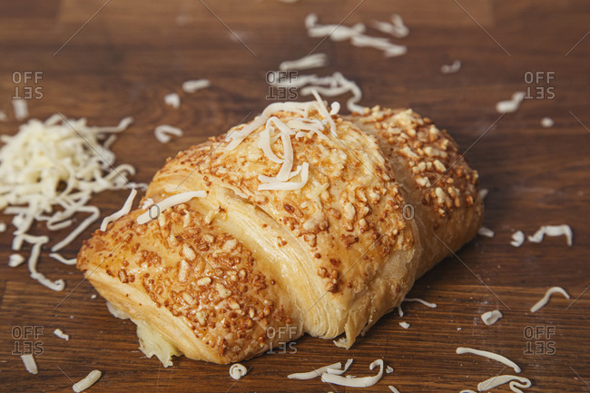 From above of delicious baked croissant with golden crust on wooden table with fresh grated cheese