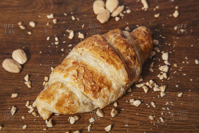 From above of delicious baked croissant with golden crust on wooden table with crumbs of almond nuts