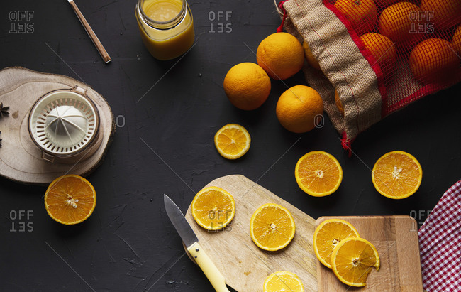 Top view of composition of halves of fresh oranges on wooden boards and mesh bag near glass jar with orange custard and plastic squeezer