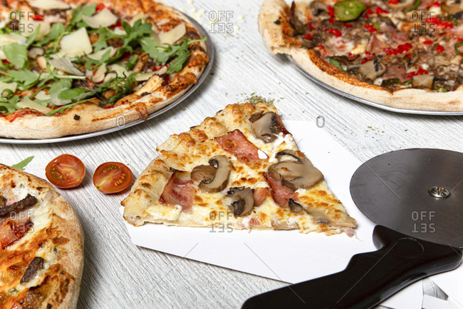 Top view of delicious pizzas with various meat and vegetables placed on white wooden table in cafe