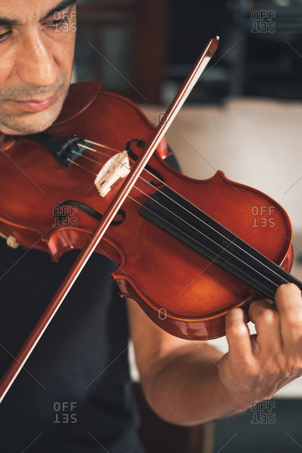 Cropped unrecognizable talented focused Hispanic male violinist playing violin during rehearsal