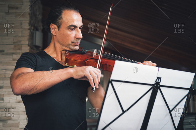 Talented Hispanic male violinist playing violin and looking at music sheets during rehearsal