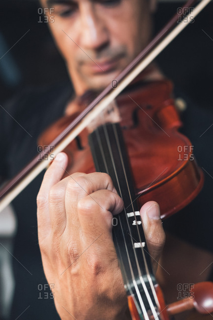 Talented focused Hispanic male violinist playing violin during rehearsal