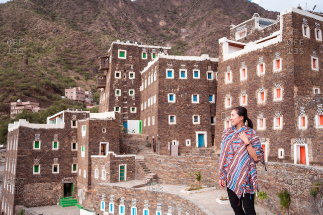 Female tourist standing on background of stone buildings with colorful windows while traveling around Rijal Almaa village in Saudi Arabia
