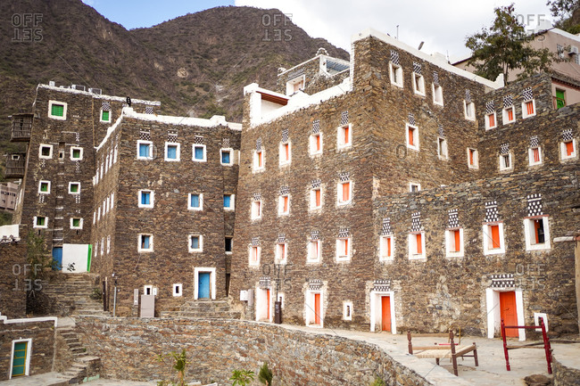 Spectacular view of aged houses with stone exterior and colorful windows located in Rijal Almaa