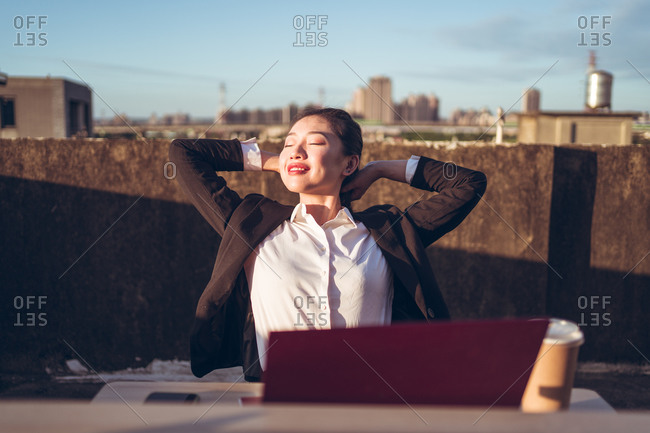 Young Asian female employee in formal wear sitting at table with laptop and cup of coffee on rooftop terrace and relaxing after remote work