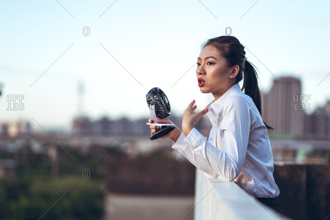 Side view of young Asian female in formal outfit using mini handheld fan while resting on rooftop in hot summer evening in city