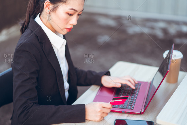 Side view of serious young Asian business lady in formal suit with credit card using laptop and smartphone during online payment while sitting at table at workplace on terrace