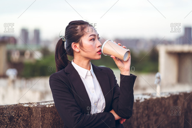 Concentrated young Asian businesswoman in formal outfit drinking disposable cup of coffee while standing on rooftop of city building